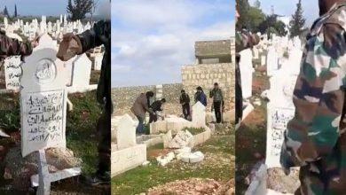 صورة عنصر من قوات نظام الأسد يعبث بقبور أقاربه جنوب إدلب ويوجه الشتائم لوالده وأشقائه المعارضين للنظام (فيديو)